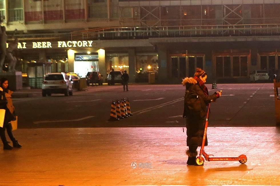 夜幕下/寒风中,她站立在路灯下,在滑板车旁不断刷屏查看代驾信息。