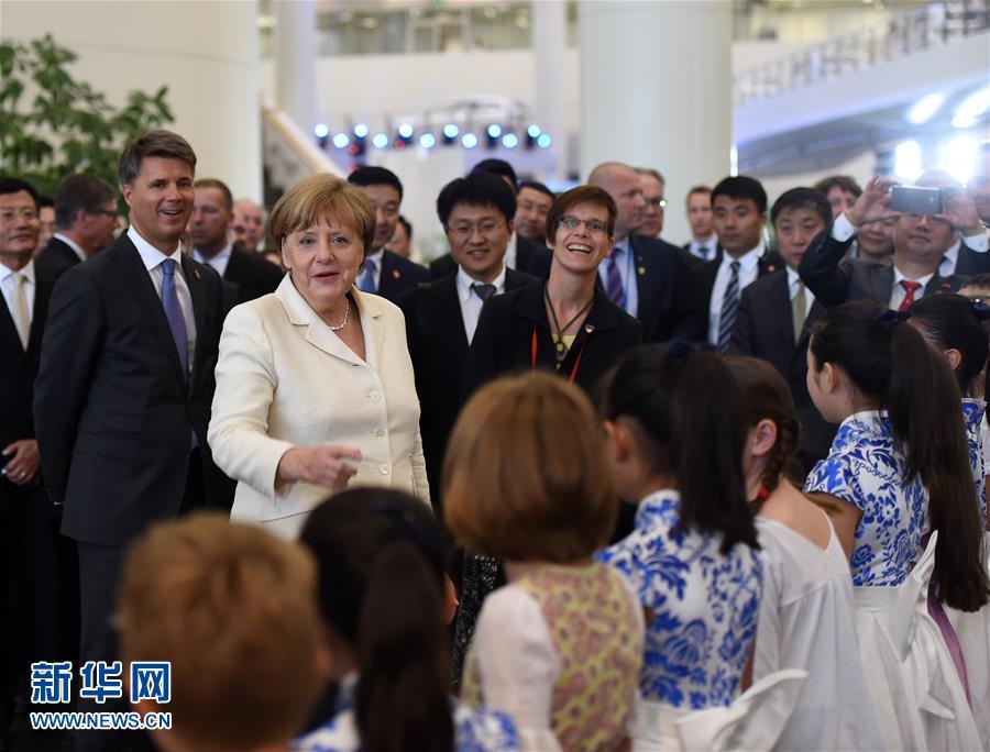 6月14日,默克尔在华晨宝马铁西工厂与唱歌的小演员交流.