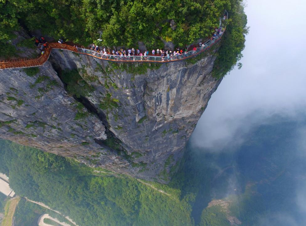 湖南张家界_图为8月1日,人们在中国湖南省张家界的观景台上行走,欣赏壮美的